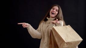 Fille d'aspect caucasien dans un chandail tricoté, tenant un groupe de sacs de cadeau et le doigt des autres expositions de côté banque de vidéos