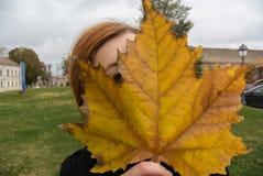 Fille d'automne se cachant derrière une feuille d'érable énorme Photos libres de droits