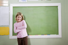 Fille d'école dans le tableau noir se tenant prêt de salle de classe Photographie stock libre de droits