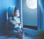 Fille d'enfant à la fenêtre rêvant le ciel étoilé à l'heure du coucher image libre de droits