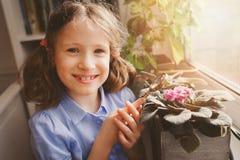 Fille d'enfant apprenant à cultiver les usines mises en pot à la maison, fleurs à la maison les explorant d'enfant avec la loupe Images stock