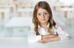 Fille d'enfant au bureau dans l'espace vide de fond de salle de classe Photo libre de droits