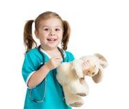 Fille d'enfant avec des vêtements de docteur avec le jouet de peluche au-dessus du blanc Photo libre de droits