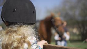 Fille d'enfant avec l'équitation de attente de casque de protection Mouvement de cardan banque de vidéos