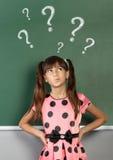 Fille d'enfant avec le point d'interrogation sur le tableau noir d'école Photo stock