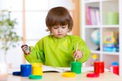 Fille d'enfant avec les peintures de couleur peintes par mains Photo libre de droits