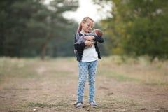 Fille d'enfant avec son frère nouveau-né sur la promenade en parc Image stock