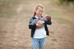 Fille d'enfant avec son frère nouveau-né sur la promenade Fin vers le haut Photo libre de droits