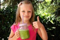 Fille d'enfant buvant le smoothie végétal vert sain - consommation saine, vegan, végétarien, aliment biologique et concept de boi photographie stock libre de droits