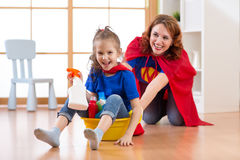 Fille d'enfant d'élève du cours préparatoire et sa mère jouant tout en faisant le nettoyage à la maison Photos stock