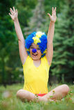 Fille d'enfant d'enfant avec les bras ouverts heureux drôles expression et guirlandes de perruque bleue de clown de partie Photographie stock libre de droits