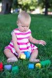 Fille d'enfant d'enfant en bas âge jouant les cubes en bois dans le jardin vert d'herbe de gazon Images libres de droits