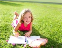 Fille d'enfant d'enfant faisant le sourire de devoirs heureux sur l'herbe Image libre de droits