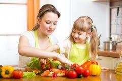 Fille d'enfant d'enseignement de mère préparant la salade Photo stock