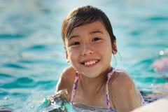 Fille d'enfant dans la piscine bleue Photo stock