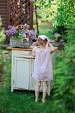 Fille d'enfant dans la robe rose de plaid près du bureau de vintage avec des lilas dans le panier Photographie stock