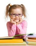 Fille d'enfant dans le livre et le sourire de lecture en verre Photo stock