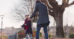 Fille d'enfant de fille apprenant l'équitation segway avec l'enseignement de papa dans la ville Future technologie moderne de tra banque de vidéos