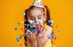Fille d'enfant de joyeux anniversaire avec des confettis sur le fond jaune photos stock