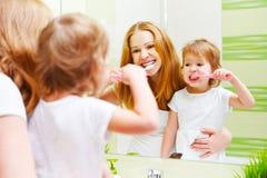 Fille d'enfant de mère et de fille balayant ses brosses à dents f de dents Photographie stock
