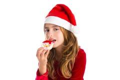 Fille d'enfant de Noël mangeant le biscuit de Noël Santa Photos stock