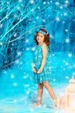 Fille d'enfant de Noël sur le fond d'arbre d'hiver, neige, flocons de neige Images stock