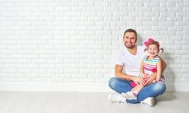 Fille d'enfant de père de famille à un mur de briques blanc vide Photos stock