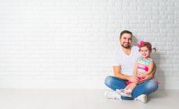 Fille d'enfant de père de famille à un mur de briques blanc vide Photo stock