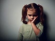 Fille d'enfant de tristesse semblant malheureuse Portrait de plan rapproché sur l'obscurité image libre de droits