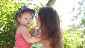 Fille d'enfant embrassant la mère heureuse joying dehors banque de vidéos