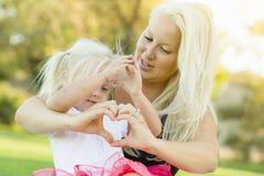Fille d'enfant en bas âge avec la mère faisant la forme de coeur avec des mains Images stock