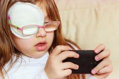 Fille d'enfant en bas âge avec le bandage sur l'oeil jouant des jeux Photographie stock libre de droits