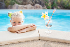 Fille d'enfant en bas âge avec le cocktail dans la piscine tropicale de plage Photo stock