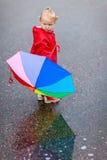 Fille d'enfant en bas âge avec le parapluie coloré le jour pluvieux Image stock