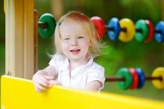 Fille d'enfant en bas âge ayant l'amusement à un terrain de jeu Photographie stock libre de droits
