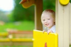 Fille d'enfant en bas âge ayant l'amusement à un terrain de jeu Photographie stock