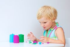 Fille d'enfant en bas âge créant avec la pâte de jeu Photo stock