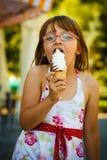 Fille d'enfant en bas âge dans des lunettes mangeant la crème glacée  Images stock