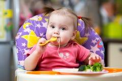 Fille d'enfant en bas âge dans un highchair pour alimenter avec la fourchette image libre de droits