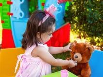 Fille d'enfant en bas âge de bébé jouant au thé extérieur alimentant son meilleur ami Teddy Bear avec la sucrerie gommeuse Photographie stock libre de droits