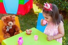 Fille d'enfant en bas âge de bébé jouant au thé extérieur buvant de la tasse avec le meilleur ami Teddy Bear Image stock