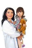 Fille d'enfant en bas âge de fixation de femme de docteur Photographie stock