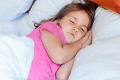 Fille d'enfant en bas âge dormant dans le lit à la maison Photos stock