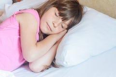 Fille d'enfant en bas âge dormant dans le lit à la maison Photographie stock libre de droits