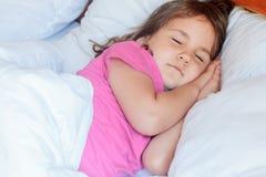 Fille d'enfant en bas âge dormant dans le lit à la maison Photo libre de droits