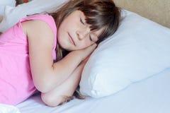 Fille d'enfant en bas âge dormant dans le lit à la maison Images stock