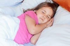 Fille d'enfant en bas âge dormant dans le lit à la maison Photographie stock