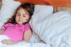 Fille d'enfant en bas âge dormant dans le lit à la maison Image stock