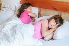 Fille d'enfant en bas âge dormant dans le lit à la maison, d'intérieur Image libre de droits