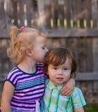 Fille d'enfant en bas âge embrassant le garçon d'enfant en bas âge Photo libre de droits